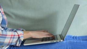 Het vrouwelijke typen op laptop toetsenbord en het controleren van slimme telefoon stock videobeelden