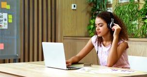 Het vrouwelijke uitvoerende luisteren aan muziek terwijl het gebruiken van laptop stock videobeelden