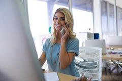 Het vrouwelijke uitvoerende spreken op mobiele telefoon terwijl het werken bij haar bureau Stock Foto's