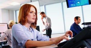 Het vrouwelijke uitvoerende werken aan computer bij bureau stock videobeelden