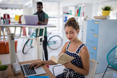 Het vrouwelijke uitvoerende werken aan laptop terwijl het lezen van een boek bij bureau stock foto's