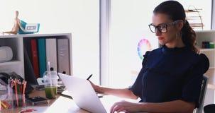 Het vrouwelijke uitvoerende werken bij haar bureau in bureau 4k