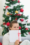 Het vrouwelijke verbergen achter de prentbriefkaar van Kerstmis Stock Foto's