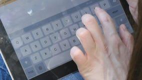 Het vrouwelijke vinger typen op het virtuele toetsenbord van tabletpc De meisjesvingers wat betreft virtuele sleutels vormen een  stock video