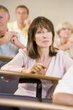 Het vrouwelijke volwassen student luisteren Stock Afbeelding