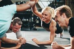 Het vrouwelijke vrienden hoge fiving terwijl het planking bij de gymnastiek royalty-vrije stock foto's