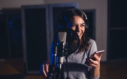 Het vrouwelijke zanger zingen in opnamestudio royalty-vrije stock afbeelding