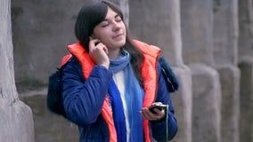 Het vrouwenmeisje sloot ogen luisterend aan muziek op smartphonehoofdtelefoons in jasje en sjaal stock video
