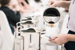 het vrouwenpersoneel giet koffie in pot om gasten te dienen die s bijwonen stock afbeeldingen