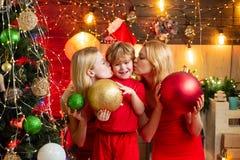 Het vrouwenrood kleedt feestelijke stemming viert Kerstmis met weinig leuke baby Familiebanden De vreugdewensen van de liefdevred stock foto's