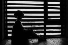 Het vrouwensilhouet bij het venster van het huis in de winter, verzacht stock afbeeldingen
