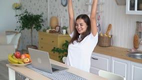 Het vrouwenwerk aangaande laptop, krijgt positief nieuws in e-mail, voelt gelukkige, opgewekte, langzame motie stock video
