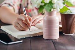 Het vrouwenwerk bij lijst met Ana van het bloemenboeket haalt koffie weg Stock Afbeelding