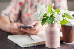 Het vrouwenwerk bij lijst met Ana van het bloemenboeket haalt koffie weg Stock Fotografie