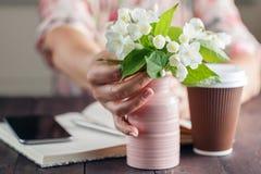Het vrouwenwerk bij lijst met Ana van het bloemenboeket haalt koffie weg Royalty-vrije Stock Afbeelding