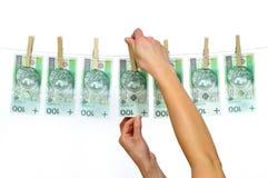 Het vuile die geld hangen van een drooglijn op wit wordt geïsoleerde Royalty-vrije Stock Foto
