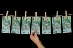 Het vuile die geld hangen van een drooglijn op zwarte wordt geïsoleerd Stock Fotografie