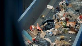 Het vuile huisvuil op een transportband, sluit omhoog stock video