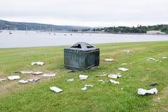 Het vuilnis van het draagstoelhuisvuil in park buiten bak die bij van de de ruïnemening van het grond de groene gras de kusttoevl royalty-vrije stock afbeelding
