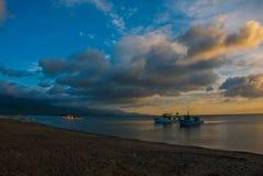 Het vulkanische zandige strand bij zonsondergang De schepen op zee Pandan, Panay, Filippijnen Royalty-vrije Stock Afbeeldingen