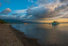 Het vulkanische zandige strand bij zonsondergang De schepen op zee Pandan, Panay, Filippijnen Stock Fotografie
