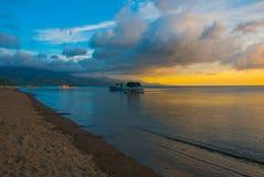 Het vulkanische zandige strand bij zonsondergang De schepen op zee Pandan, Panay, Filippijnen Royalty-vrije Stock Afbeelding