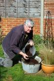 Het vullen van de bejaarde container met compost Stock Foto's