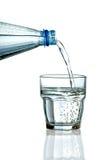 Het vullen van een glas met water op witte achtergrond Stock Fotografie