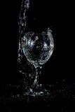 Het vullen van een glas met water op witte achtergrond Stock Afbeelding