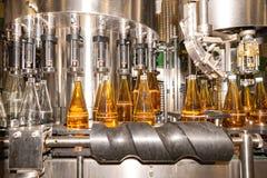 Het vullen van flessen met sap Het bottelen van dranken Bottelarij royalty-vrije stock fotografie