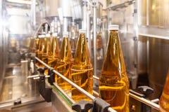 Het vullen van flessen met sap Het bottelen van dranken Bottelarij royalty-vrije stock foto