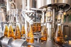 Het vullen van flessen met sap Het bottelen van dranken Bottelarij royalty-vrije stock afbeelding