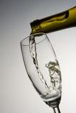 Het vullen van glas met witte wijn stock fotografie