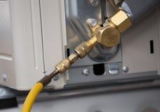 het vullen van koelmiddel aan airconditionerklep stock foto's