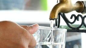 het vullen van water in glas stock videobeelden