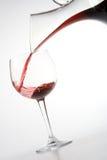 Het vullen van wijnglas vanaf karaf stock foto