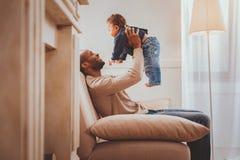 Het waakzame papa spelen met zijn zoon stock foto