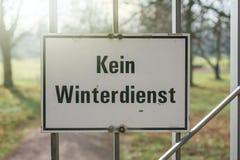 Het waarschuwingsbord met de Duitser etiketteert 'Geen de winterdienst bij de ingang van een park stock afbeelding