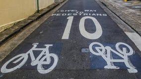 Het waarschuwingsbord voor een fietser om aan voetgangers en maximum snelheid, niet meer dan 10 km/h uiting te geven, het toont g stock afbeelding