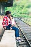 Het wachten op de trein Aziaat met een kind op de sporen Stock Afbeeldingen