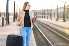 Het wachten op Trein Vrouw die elektronisch kaartje kopen stock afbeeldingen