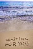 Het wachten op u geschreven in een zandig tropisch strand Royalty-vrije Stock Foto's