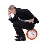 Het wachten van de zakenman gezet op een klok stock afbeeldingen