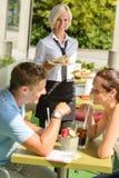 Het wachten van het paar de lunchrestaurant van de serveerstersandwich Stock Afbeeldingen