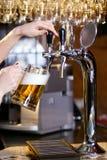 Het wachten vrouwen gietend bier Royalty-vrije Stock Afbeeldingen