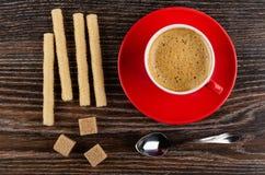 Het wafeltje rolt, kop met koffieespresso op schotel, suiker, lepel op lijst Hoogste mening stock foto
