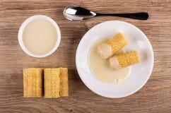 Het wafeltje rolt met condens in schotel, glaskom met melk, lepel op lijst Hoogste mening stock foto's