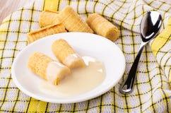 Het wafeltje rolt met condens in schotel, wafeltjebroodjes op servet op lijst stock afbeelding
