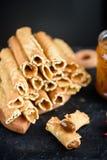 Het wafeltje rolt, smakelijk en geurig, met gekookte condens op een zwarte lijst stock foto's