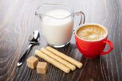 Het wafeltje rolt, suiker, lepel, kruik melk, kop met koffieespresso op houten lijst stock afbeelding